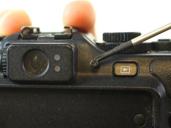 Remove the screw on the right side of the view finder on the back side of the camera.