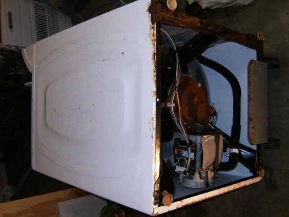 Image 3/3: For ease of working on the bottom parts, lay the washer on its side.