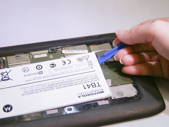 Pry the battery out of the device with the  plastic opening tool.