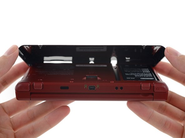 Prying from the thumb slots on each side, pull the rear panel off the back of the device.