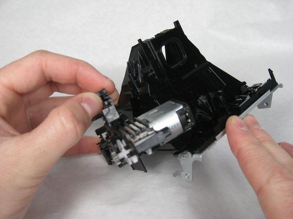 Remove the plastic extension by pulling it from the slot in the rear of the camera.