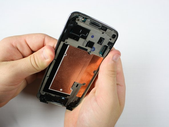 Image 2/3: Apply pressure to the battery slot on back of the phone to separate the midframes.