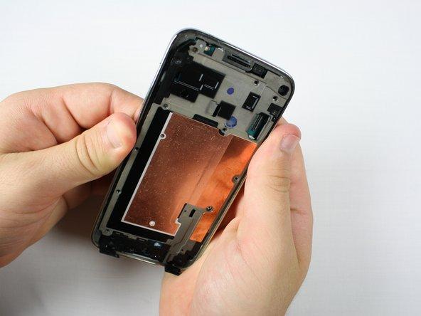 Drücke am Akkufach auf der Rückseite des Smartphones um den Mittelrahmen zu lösen.