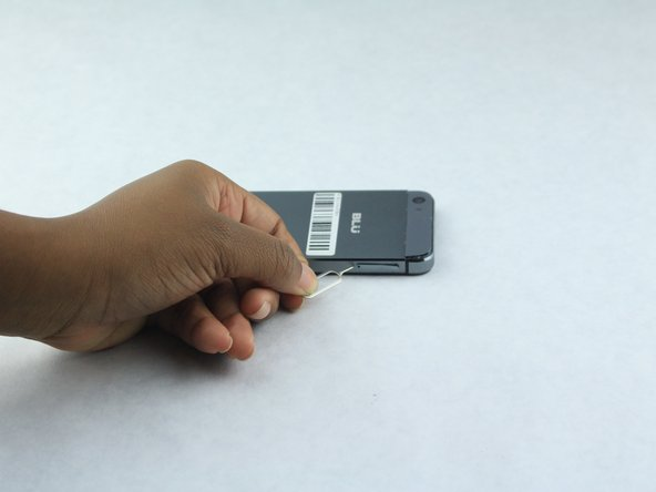 With the use of the SIM Card Eject Tool gently insert the tool into the hole.
