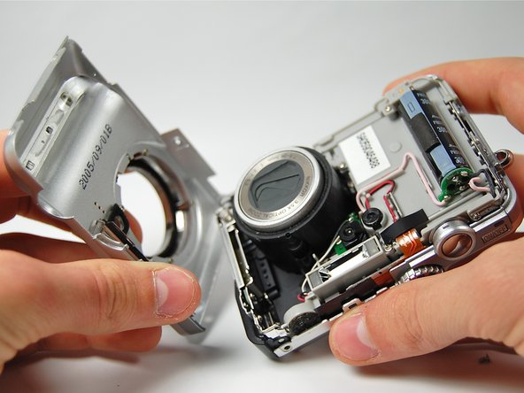 Image 3/3: Gently pull apart the front casing from the rest of the camera.