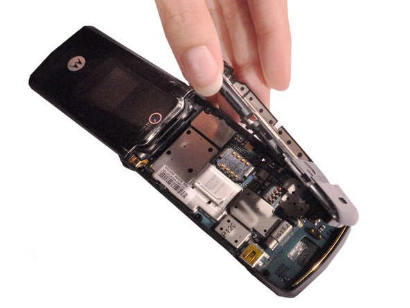Use hands to remove the unscrewed rear frame of the phone.