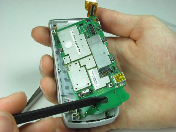 Image 1/2: Gently remove the logic board from the phone casing.
