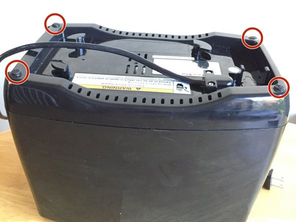 Image 1/3: Use needle nose pliers to remove the rubber screw covers located on the four corners of the bottom of the toaster.