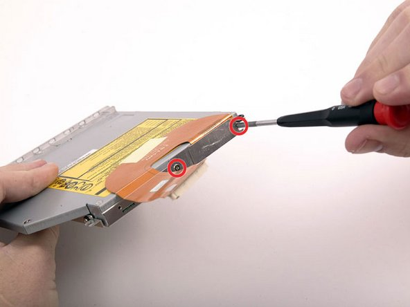 Image 1/1: Remove the two Phillips screws securing the metal bracket and cable to the back of the optical drive.