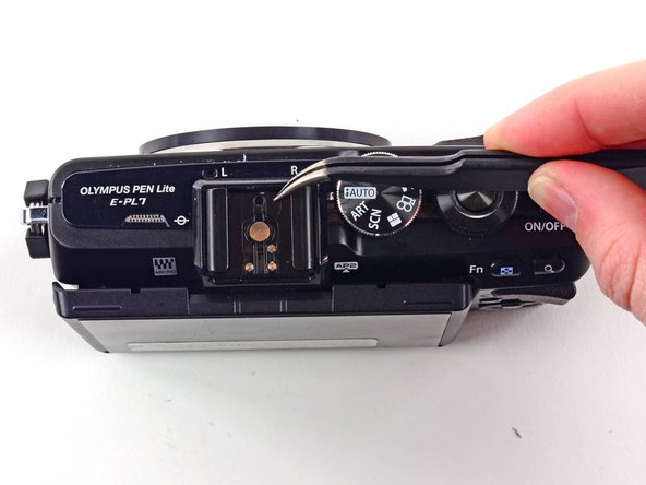 Use tweezers to remove the metal clip from the external flash mount.