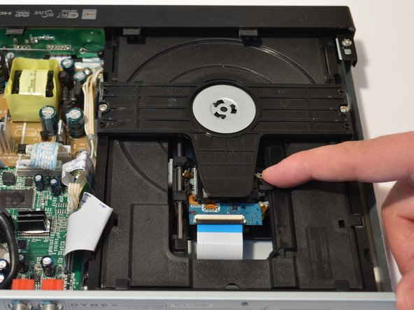 To access the optical lens, pull back the optical drive as shown in the pictures located on the two metal rails.