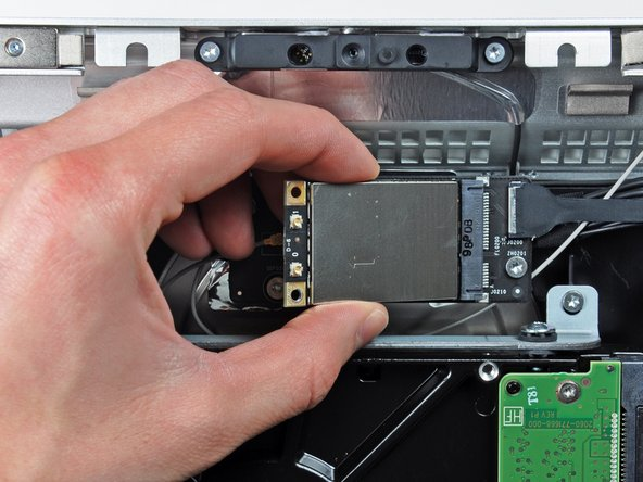Pull the AirPort card away from its socket and remove it from the iMac.