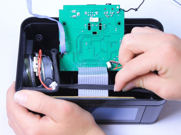 Lift the adhesive strip that holds down the grey ribbon cable which attaches to the circuit board and the LCD screen.
