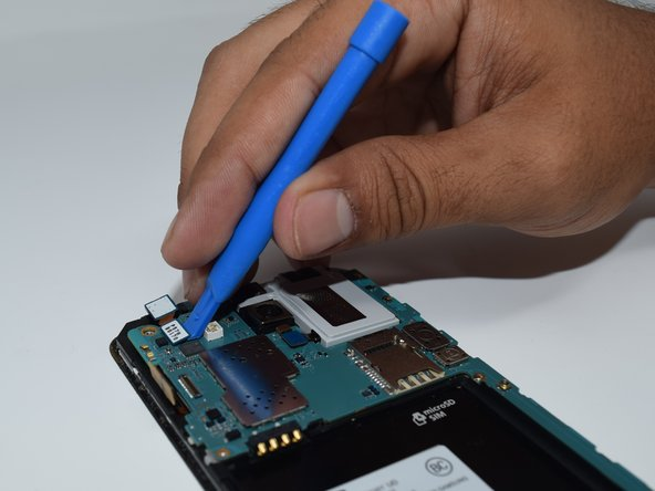 Use a plastic spudger to disconnect the ribbon cable from the motherboard.