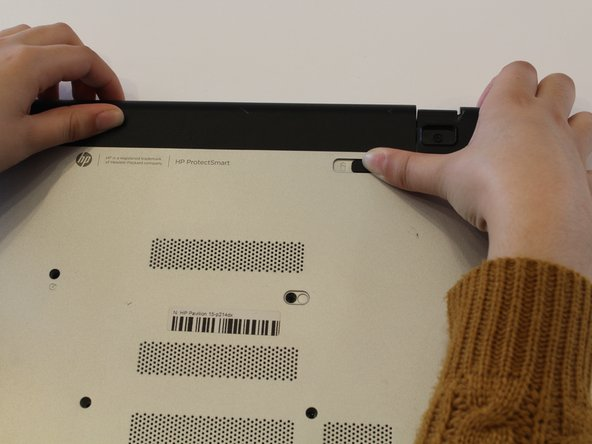 Slide the battery release latch (the upper right-hand switch on the laptop's bottom) to the left.