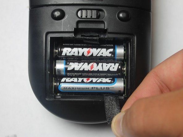 Image 1/3: If applicable, pull on the black ribbon to release all six Triple A batteries at the same time.