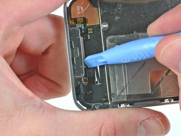 С помощью пластиковой лопатки откройте зажим разъёма, держащий шлейф кнопки Home.