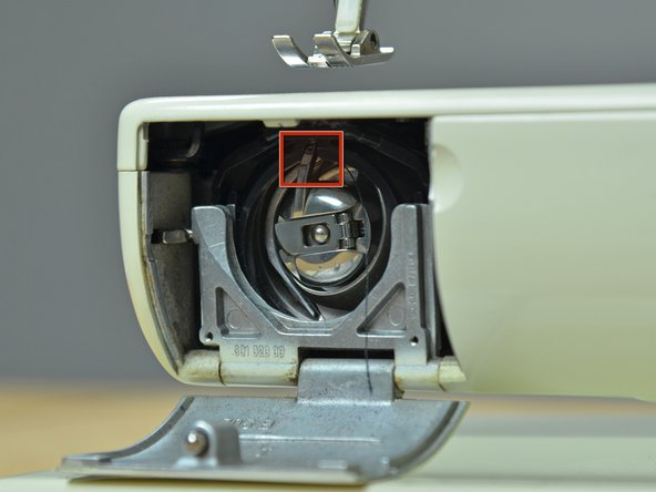 Align the metal arm on the bobbin case so that it sits in the slot in the machine.