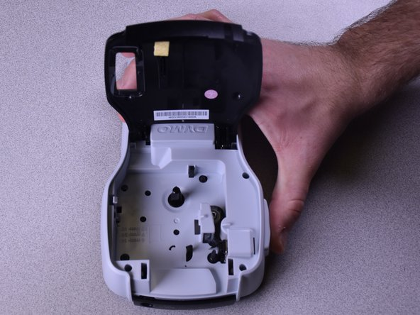 Open the label cartridge compartment and remove any current label cartridge to reveal your label cutting blade.
