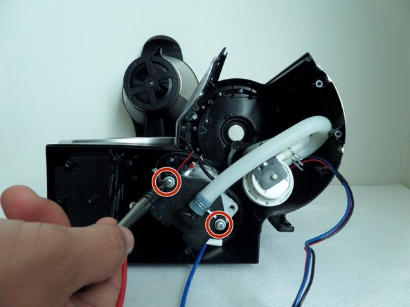 Remove the two 0.8 cm screws with Phillips #1 screwdriver.