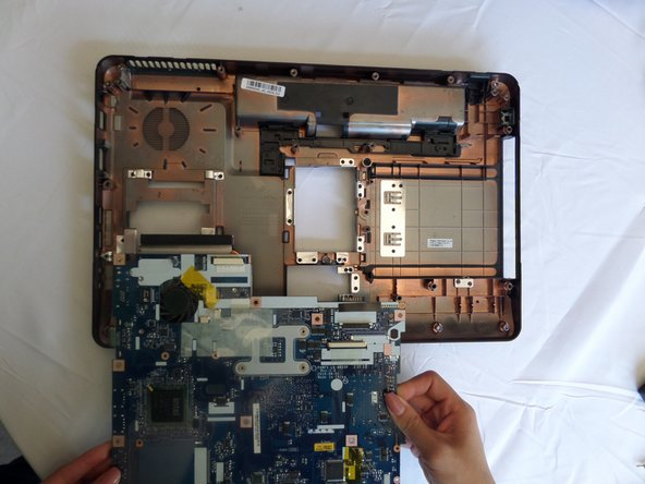 Lift the circuit board  out of the back panel and turn it over so the fan is facing up.