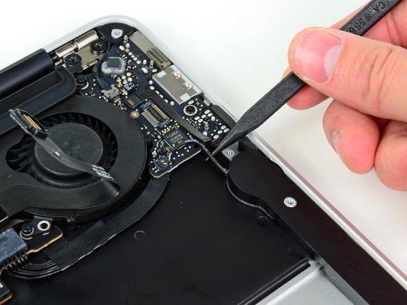 Fädle das Kabel zum linken Lautsprecher mit der Spudgerspitze aus dem Einschnitt in der Kante des I/O Boards.