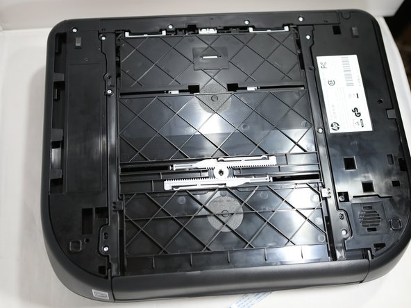 Flip the printer upside down so that the paper tray is located at the bottom of the HP Envy 4520 is accessible.