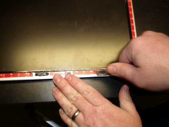 While applying pressure with the flat side of the spudger, drag the spudger across all of the attached adhesive strips.