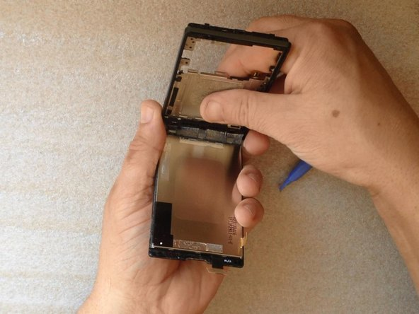 With a plastic tool, carefully separate the LCD display from the touch screen.