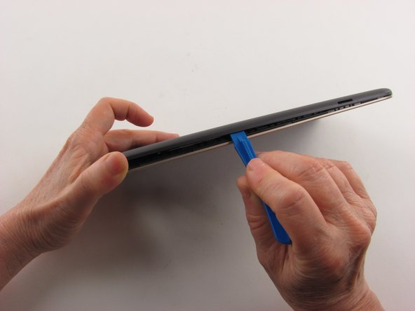 Insert a plastic opening tool into the seam between the rear case and the screen.