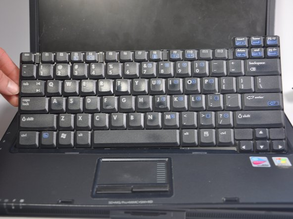 Flip the keyboard away from the monitor, rotating it so that the keys are face down on the mousepad. Remove the black cord at the bottom of the keyboard that connects it to the motherboard. The keyboard is now free and can be removed.