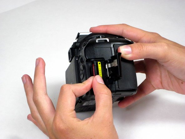 Using thumb and forefinger, gently remove the SD card from its slot.