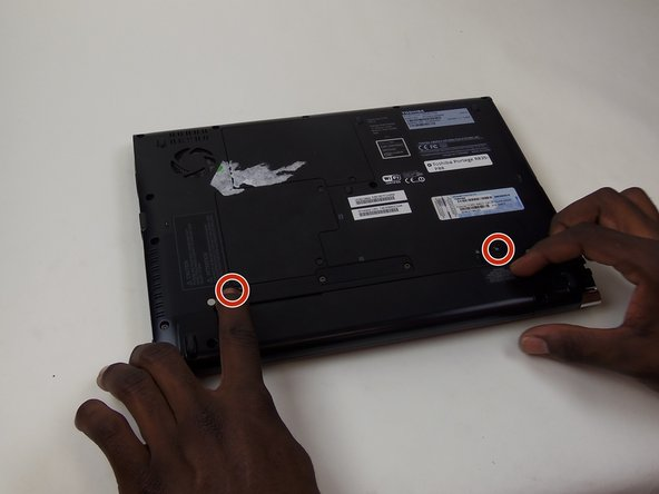 Remove the battery by pressing the two buttons inward and pulling the battery out.