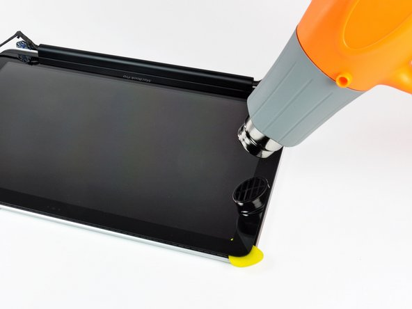 Image 1/2: Use a heat gun to soften the adhesive under the black strip along the left side of the front glass panel.