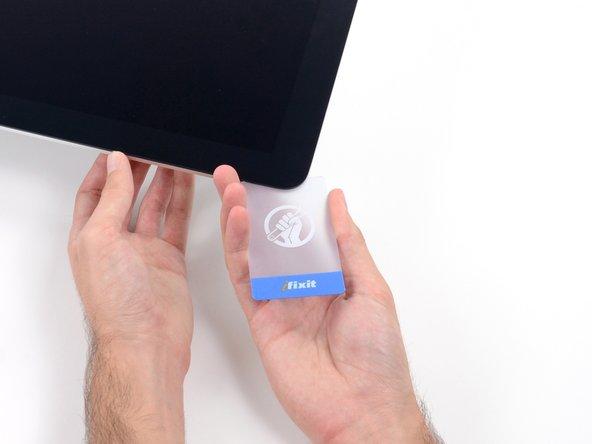 Schiebe eine zweite Karte in den Spalt zwischen Display und Rahmen an der oberen linken Ecke des iMacs.