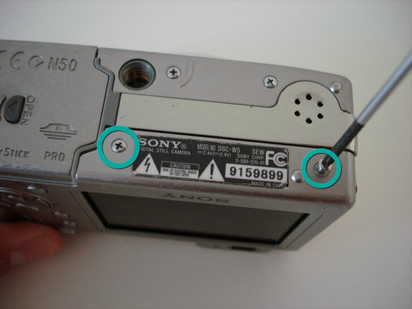 Remove the two screws that are adjacent to the warning label, which is on the underside of the camera.