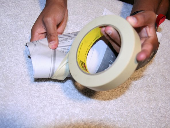 Wrap the adhesive tape around the newspaper tightly to keep pressure on the tear until the glue dries.