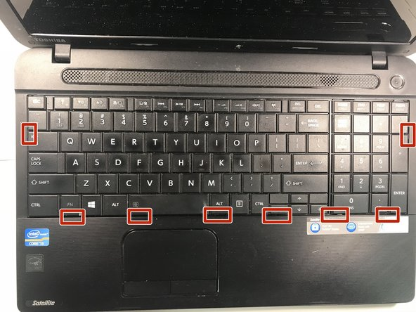 Looking at the keyboard, locate the eight clips that hold it in place.