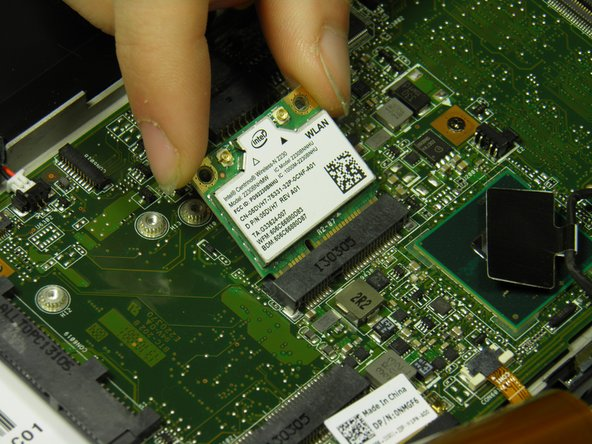 Angle the wireless WLAN card upward and remove it.