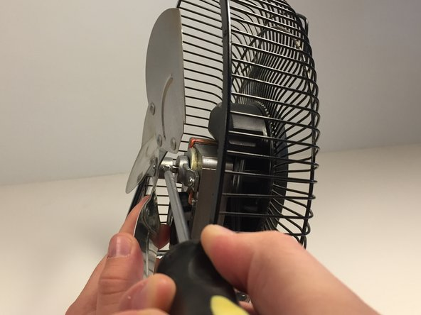 Remove the fan blade by loosening the screw on the shaft while pulling up.