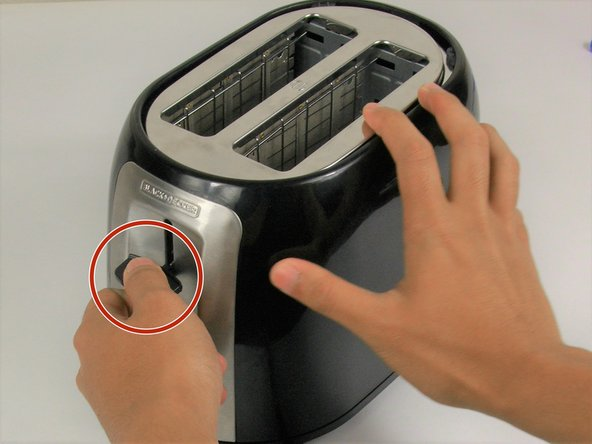 Image 1/1: Remove the carriage lever by pulling it away from the toaster.