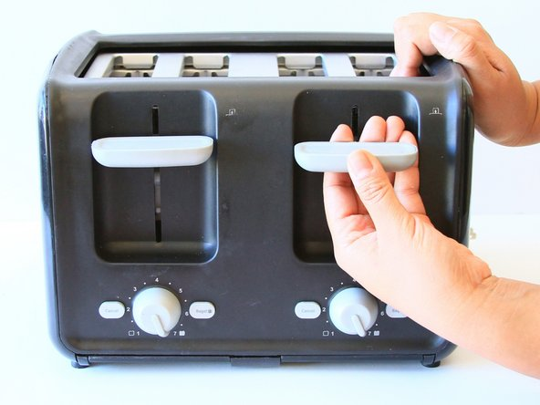 Forcefully pull the slot lever away from the toaster by keeping parallel to the table.