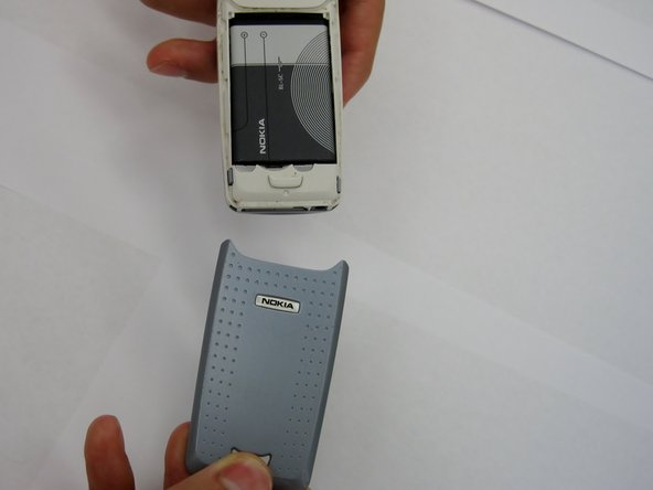 Remove the back cover plate of the phone.  To do this press down the lock as you slide the cover toward the bottom of the phone.