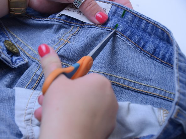 Using the seam ripper or a pair of scissors, break the two seams to loosen the lining along the fabric.
