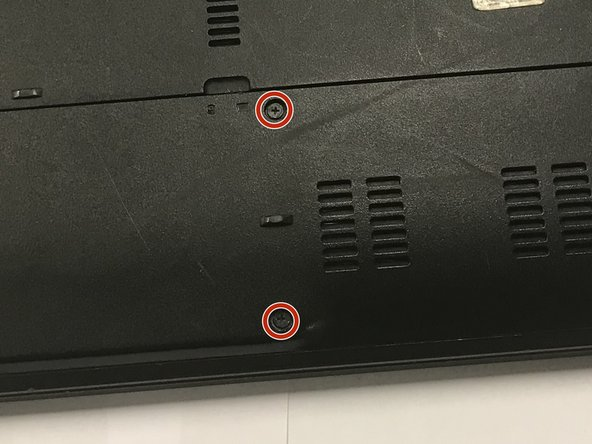 Remove the two 6.0mm Phillips #00 screws from the back cover.