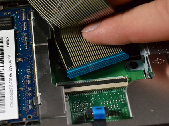 Lift the keyboard up and off of the motherboard, detaching the blue end of the ribbon from the connector.