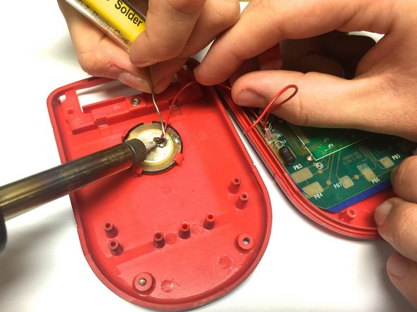 Using a soldering iron, solder both red wires to their appropriate connections.