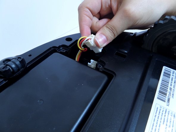 Using one hand, pinch the white plastic connector where the battery's wiring connects the POWERbot.  Pull up to disconnect.