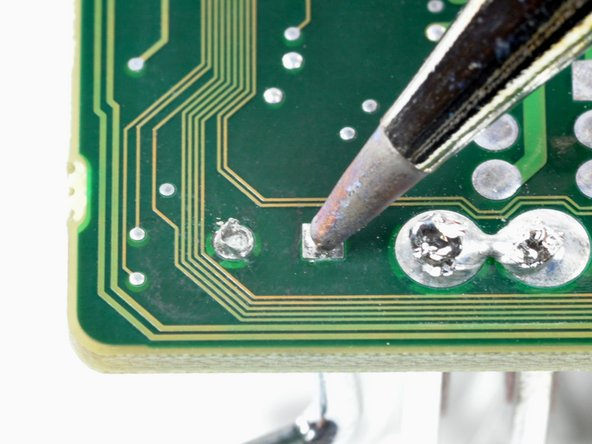 To open the hole blocked by solder, heat the solder pad with the tip of a soldering iron. Push through the molten solder from the other side with a staple or sewing needle.