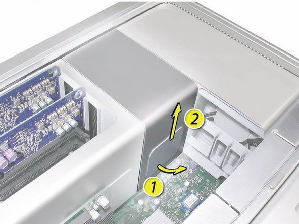 Image 2/2: Place the fingers of one hand under the lip of the heatsink cover nearest the logic board. Lift the lip slightly toward the media shelf to release the tabs and magnets under the top face of the cover.